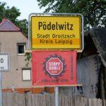 Dorfeingangsschild von Pödelwitz mit Protestfahne