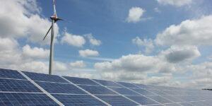 Solarpanele mit Windrad im Hintergrund