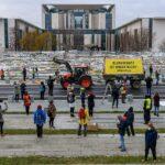 Bäuer:innen demonstrieren mit ihrem Traktor vor dem Kanzleramt für eine Agrarwende. Im Hintergrund 10.000 ausgedruckte Fußabdrücke, die Einzelpersonen eingeschickt haben.